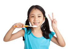 Little asian girl show victory sign with toothbrush Stock Images
