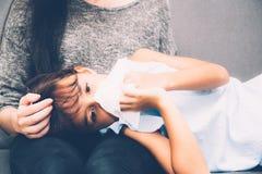Little asian girl is sick weak lying on sofa with mother of take care. Little asian girl is sick weak lying on sofa with mother of take care and touching Royalty Free Stock Photo