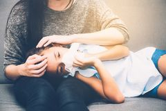 Little asian girl is sick weak lying on sofa with mother of take care. And touching forehead in living room - family health concept stock images