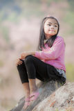 Little asian girl sit on the rock with pink sakura Stock Photos