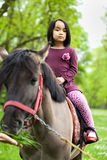 Little Asian girl sitting on a horse Stock Photo