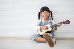 little asian girl sitting playing ukulele on white background with copy space stock photo