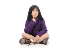 Little asian girl sitting and thinking Stock Photo