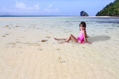 Little asian girl sitting at tropical beach Stock Photos