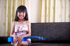 Little asian girl sitting with ukulele Royalty Free Stock Image