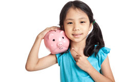 Little asian girl smile point to piggy bank Royalty Free Stock Image
