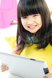 Little asian girl smiles with tablet computer Royalty Free Stock Photos
