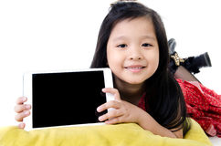 Little asian girl smiles with tablet computer Royalty Free Stock Photography
