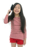 Little asian girl smiling and brushing hair Royalty Free Stock Image