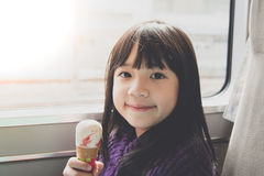 Little asian girl smiling  and eating ice cream Stock Photos