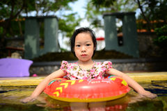 Little Asian girl swims in a pool in Royalty Free Stock Photos