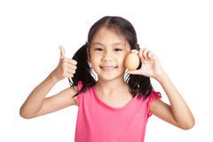 Little asian girl thumbs up with an egg in hand Royalty Free Stock Image