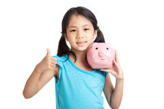 Little asian girl thumbs up with piggy bank Royalty Free Stock Image