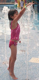 Little asian girl touching water at waterpark Royalty Free Stock Photo