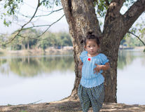 Little asian girl with tree near lagoon Royalty Free Stock Photos
