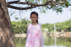 Little asian girl with tree near lagoon Stock Images