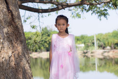 Little asian girl with tree near lagoon Royalty Free Stock Photo