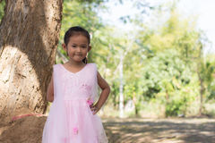 Little asian girl with tree near lagoon Royalty Free Stock Image
