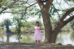 Little asian girl with tree near lagoon Royalty Free Stock Photography