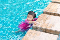 Little Asian girl try swimming alone in swimming pool, outdoor stock photos