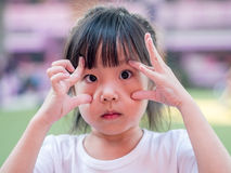 Little asian girl try to show big eyes Royalty Free Stock Photo