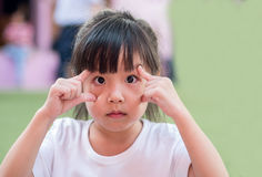 Little asian girl try to show big eyes Stock Image