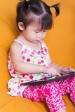 Little asian girl using digital tablet, child finger point at co Stock Photo
