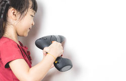Little asian girl is using screwdriver to fix the house. Easy DIY tool that even a little girl can use. Girl is making a hole in her white wall with copy space royalty free stock image