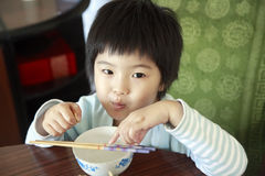 Little asian girl waiting for lunch. Royalty Free Stock Photography
