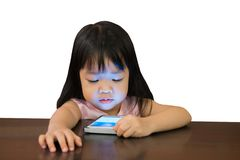 Little asian girl watching mobile phone on white background with. Girl with black long hair watching smartphone on wooden table Royalty Free Stock Images
