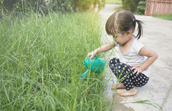 Little asian girl watering plants Stock Photo