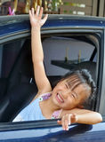 Little asian girl waving hand in a car Royalty Free Stock Images