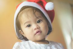 Little Asian girl wearing a Santa Cross hat. Has a cute and innocent look. royalty free stock photos