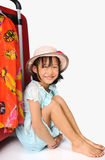 Little asian girl in weave hat sitting near a huge travel red su. Itcase in white background Royalty Free Stock Photo