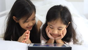 Little Asian girls enjoy with tablet stock video footage