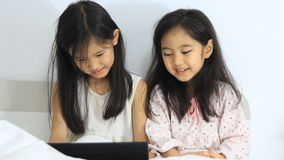 Little Asian girls laughing with tablet stock video footage
