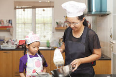 Little asian girls and mother making sponge cake. Little asian girl mixing flour to making sponge cake in kitchen royalty free stock photos