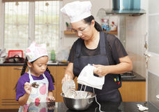 Little asian girls and mother making sponge cake. Little asian girl mixing flour to making sponge cake in kitchen stock image