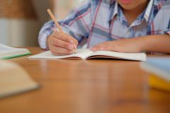 Little asian kid boy schoolboy writing drawing on notebook. child children doing homework. Young little asian kid boy schoolboy writing drawing on notebook stock photo