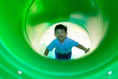 Free Little Asian Kid Climbing Up The Slide At The Playground Under The Sunlight In Summer Stock Images - 179481354