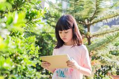 Asian kid girl using tablet watching video. Little asian kid girl using modern tablet device for e-learning and watching video. Daylight outdoor garden trees Royalty Free Stock Photos