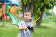 Little Asian kid holding a radio remote control controlling han Stock Images
