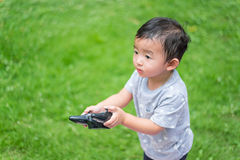 Little Asian kid holding a radio remote control controlling han Royalty Free Stock Photography