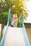 Little Asian kid playing slide at the playground. Under the sunlight in summer, Kids play on school yard. Happy kid in kindergarten, color tone, shallow DOF royalty free stock image