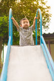 Little Asian kid playing slide at the playground. Under the sunlight in summer, Kids play on school yard. Happy kid in kindergarten, color tone, shallow DOF Royalty Free Stock Images