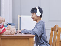 Little Asian kid smiling, wearing headphones during online learning. Chinese boy smiling, wearing headphones during online learning Stock Photo