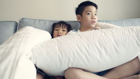 Little Asian kids watching TV on sofa stock footage