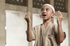 Little asian muslim boy is praying with raise hand Royalty Free Stock Photo