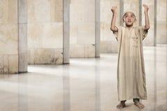 Little asian muslim boy raising hand and praying Royalty Free Stock Photography