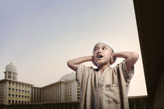 Little asian muslim boy wearing cap praying. With mosque at background Royalty Free Stock Images